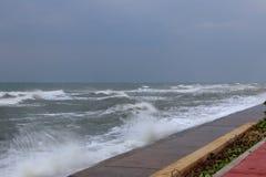 Rolls av den slående barriären för våg av en strand på en molnig dag Royaltyfria Foton