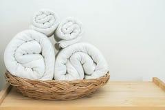 Rolls av den vita bomullshandduken på korg i sovrummet för bad royaltyfri fotografi