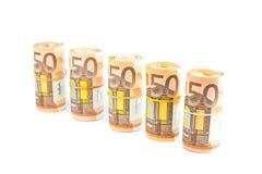Rolls av euroanmärkningar i rad på vit Arkivfoto