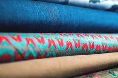 Rolls av färgrikt tyg som en vibrerande bakgrund Fotografering för Bildbyråer