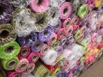 Rolls av texturerat dekorativt inpackningspapper av olika färger och skuggor på hyllan i materiel arkivbilder