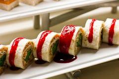 Rolls av tunna tortillor som är välfyllda med grönsaker under tomatsau royaltyfri fotografi