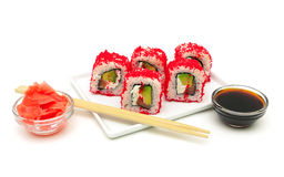 Rolls with avocado, salmon and fish roe on a plate on a white ba Royalty Free Stock Photography