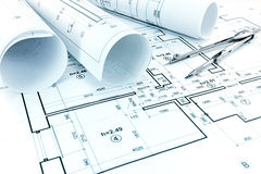 Rolls of blueprints, drawing compass and architectural plan of a Stock Photography