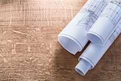 Rolls of blueprints on wooden oaken board. Construction concept Royalty Free Stock Image