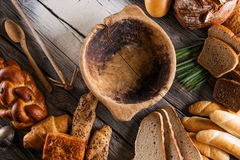 Rolls and breads on wooden table with wooden bowl, background for bakery or market Stock Photos