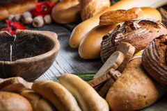 Rolls and breads on wooden table with wooden bowl, background for bakery or market Royalty Free Stock Photos