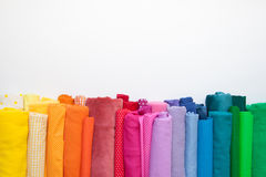 Rolls of bright colored fabric on a white background. Royalty Free Stock Images