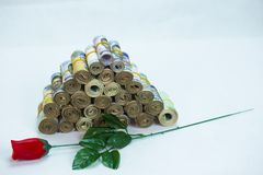 Rolls and Bundles of Naira Cash local currencies in a pyramid heap with a stem of Rose flower stock image