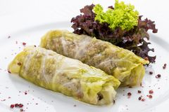 Rolls of cabbage with meat and vegetables on a white plate stock photos