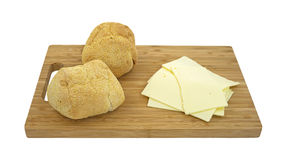 Rolls and cheese on cutting board Stock Photo