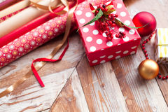 Rolls of Christmas wrapping paper with ribbons, gifts and bolls Royalty Free Stock Images