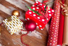 Rolls of Christmas wrapping paper with ribbons, gifts and bolls Royalty Free Stock Photo