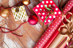 Rolls of Christmas wrapping paper with ribbons, gifts and bolls Stock Image