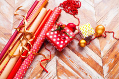 Rolls of Christmas wrapping paper with ribbons, gifts and bolls Stock Photo