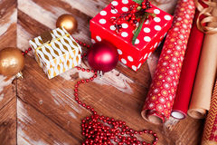 Rolls of Christmas wrapping paper with ribbons, gifts and bolls Royalty Free Stock Image