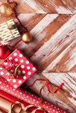 Rolls of Christmas wrapping paper with ribbons, gifts and bolls Stock Images