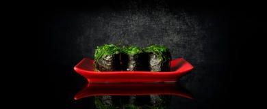 Rolls with chuka algae. On red dish and black background Stock Photo