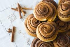 Rolls Cinnabon avec de la cannelle et le sucre sur la nappe brodée Photo stock