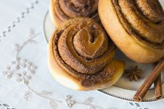 Rolls Cinnabon avec de la cannelle et le sucre sur la nappe brodée Image libre de droits