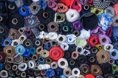 Rolls of cloth on the market with different colors. Large amount of different colored sewing thread. Wide view Stock Photos