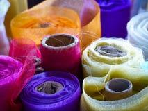 Rolls colorée de matériel sur une stalle du marché Photos libres de droits