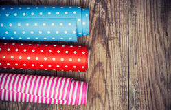 Rolls of colored wrapping paper. On wooden background Stock Photo
