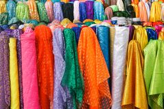 Rolls colorful of brightly coloured fabrics and cloths royalty free stock image