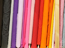 Rolls of colorful cloth for sale. Rolls of colored fabrics for sale by the merchant of fine fabrics Stock Photos