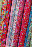 Rolls of colorful printed cloths. Close up of colorful printed rolls of cloth, vertical format Royalty Free Stock Images
