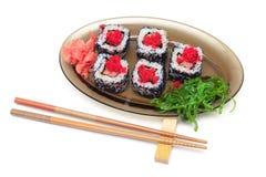 Rolls com caviar, salada do chuka em uma placa e hashis em um wh Fotos de Stock Royalty Free