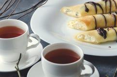 Rolls com requeijão e chocolate ao lado de dois copos do chá Close-up cropping imagem de stock royalty free