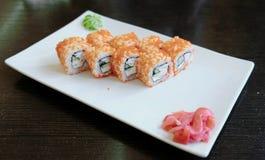 Rolls con el caviar con el jengibre y el wasabi conservados en vinagre en una placa rectangular blanca Imagenes de archivo