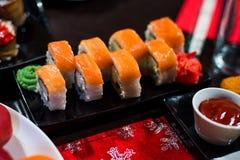 Rolls con il pesce e l'avocado sul piatto con salsa, zenzero, wasabi Immagine Stock Libera da Diritti