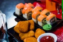 Rolls con il pesce su un piatto con salsa e le pepite di pollo Fotografia Stock