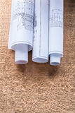 Rolls of construction drawings on wooden oaken. Board maintenance concept Royalty Free Stock Images