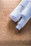 Rolls of construction plans on wooden oaken board Royalty Free Stock Photo