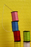 Rolls of cotton with needle. Close view of stack of colorful rolls of cotton with needle Royalty Free Stock Photography