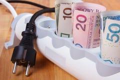 Rolls d'argent polonais de devise dans la bande de courant électrique et la prise déconnectée, coûts énergetiques Image libre de droits