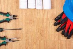 Rolls de diagramas o de modelos eléctricos, casco protector con los guantes y las herramientas del trabajo, accesorios para los t Imagen de archivo