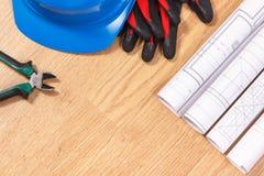 Rolls de dibujos eléctricos, casco azul protector con los guantes y herramientas del trabajo, accesorios para los trabajos del in Fotos de archivo