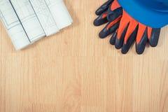 Rolls de dibujos eléctricos, casco azul protector y guantes, accesorios para los trabajos del ingeniero Fotos de archivo