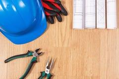 Rolls de dibujos o de modelos eléctricos, casco protector con los guantes y las herramientas del trabajo, accesorios para los tra Foto de archivo libre de regalías