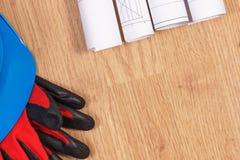Rolls de dibujos o de diagramas eléctricos y casco azul protector con los guantes Imágenes de archivo libres de regalías