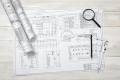 Rolls de los bosquejos, de la lupa, de la regla y del prolongador del dibujo están en superficie de madera Imagen de archivo