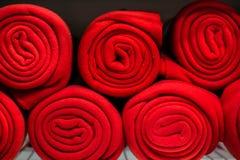 Rolls de muitas mantas vermelhas na prateleira imagem de stock royalty free