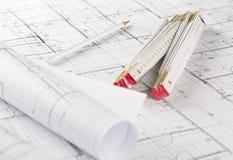 Rolls de planos arquitetónicos da construção de casa do modelo com a régua do lápis e de dobradura no fundo do modelo fotografia de stock