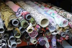 Rolls de telas coloridas na loja da tela, com ornamento imagens de stock