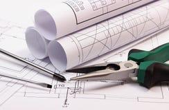 Rolls dei diagrammi e degli strumenti del lavoro sul disegno di costruzione elettrico della casa Fotografie Stock Libere da Diritti