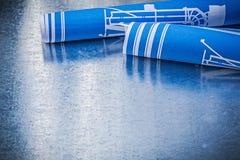Rolls dei disegni di costruzione blu su configurazione metallica del fondo Fotografia Stock Libera da Diritti